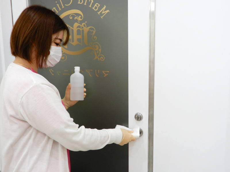 横浜マリアクリニックの入口ドアの消毒